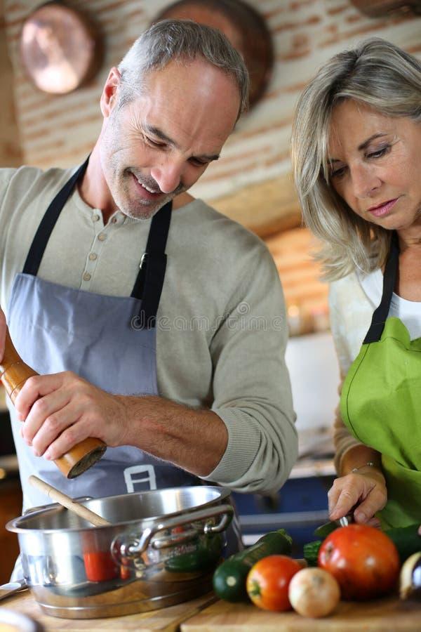 Het hogere paar koken samen in keuken stock foto