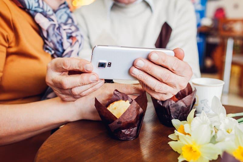 Het hogere paar maakt een selfie gebruikend een telefoon in de koffie Het vieren verjaardag Close-up royalty-vrije stock foto