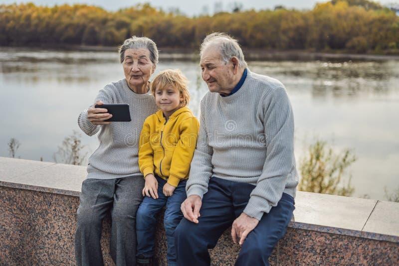 Het hogere paar met groot-kleinzoon neemt een selfie in het de herfstpark Groot-grootmoeder, groot-grootvader en groot royalty-vrije stock fotografie