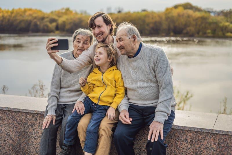 Het hogere paar met met kleinzoon en de groot-kleinzoon nemen een selfie in het de herfstpark Grote groot-grootmoeder, royalty-vrije stock afbeeldingen