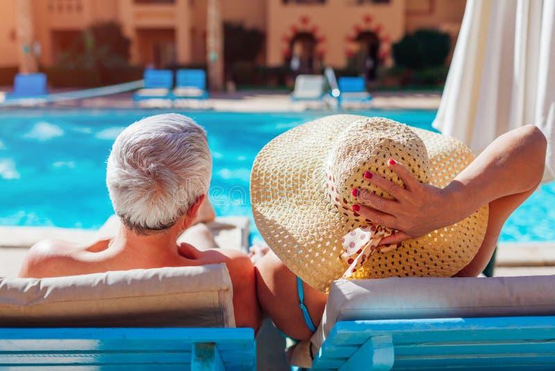 Het hogere paar ontspannen door zwembad die op chaise-longues liggen Mensen die de zomer van vakantie genieten stock foto's