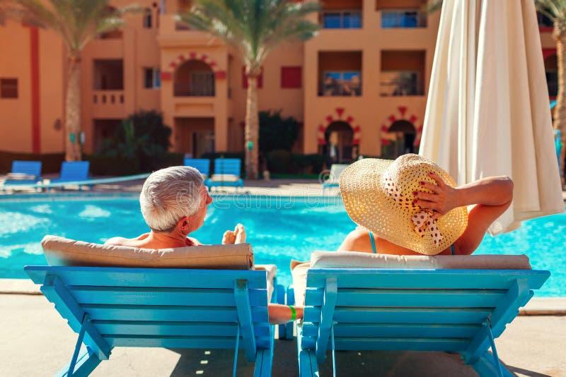 Het hogere paar ontspannen door zwembad die op chaise-longues liggen Mensen die de zomer van vakantie genieten royalty-vrije stock foto's