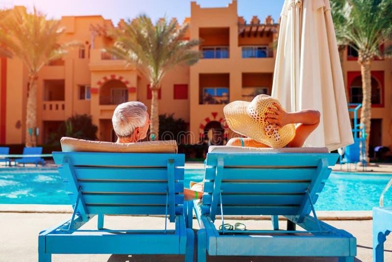 Het hogere paar ontspannen door zwembad die op chaise-longues liggen Mensen die de zomer van vakantie genieten royalty-vrije stock fotografie