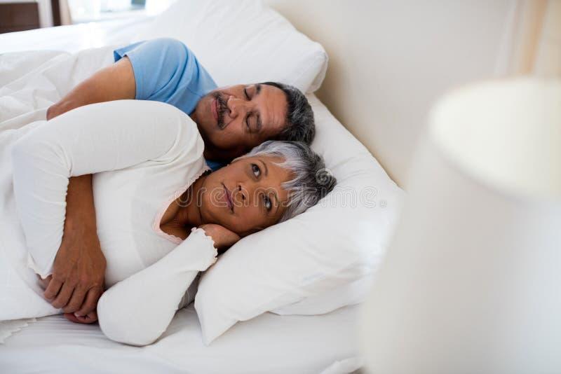 Het hogere paar ontspannen samen op bed in slaapkamer stock afbeeldingen