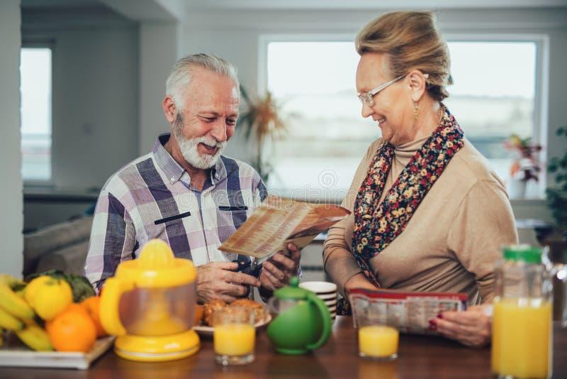 Het hogere paar snijdt de coupons voor de kortingen van de krant royalty-vrije stock afbeelding