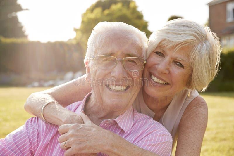 Het hogere paar in tuin, die bij camera glimlachen, sluit omhoog stock afbeelding