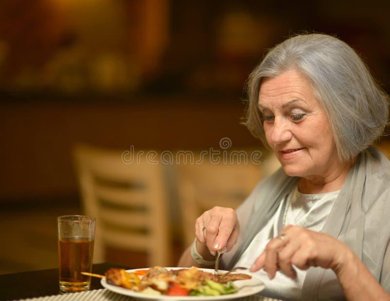 Het hogere vrouw eten stock afbeelding