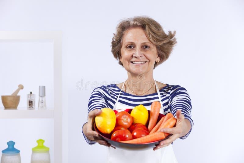 Het hogere vrouw koken stock foto's