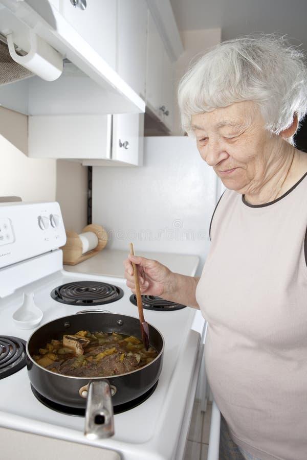 Het hogere vrouw koken stock fotografie