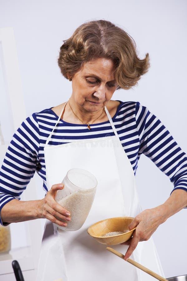 Het hogere vrouw koken stock foto
