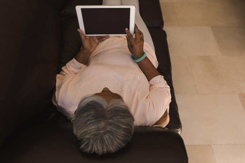 Het hogere vrouw ontspannen op een bank terwijl het gebruiken van digitale tablet in woonkamer royalty-vrije stock afbeeldingen