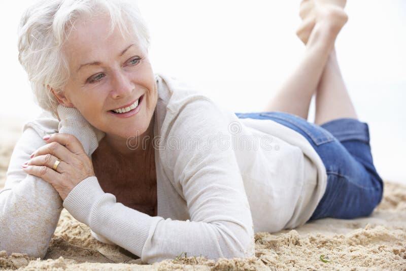 Het hogere vrouw ontspannen op strand royalty-vrije stock afbeeldingen
