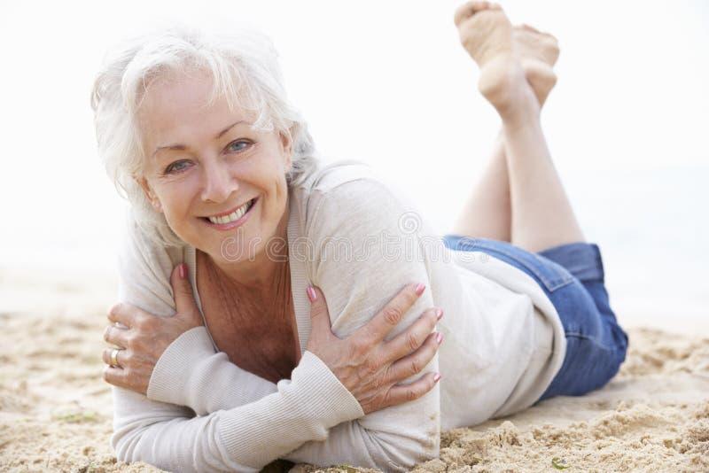 Het hogere vrouw ontspannen op strand royalty-vrije stock foto's