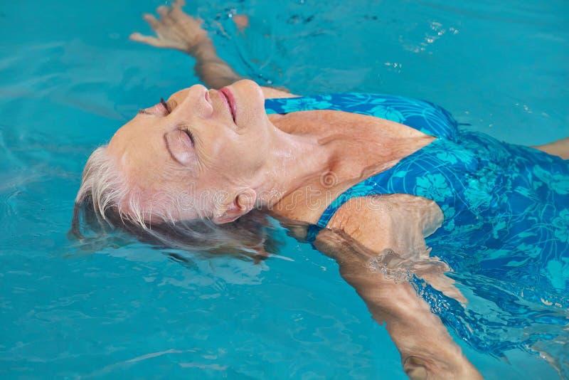 Het hogere vrouw ontspannen in zwembad royalty-vrije stock afbeeldingen