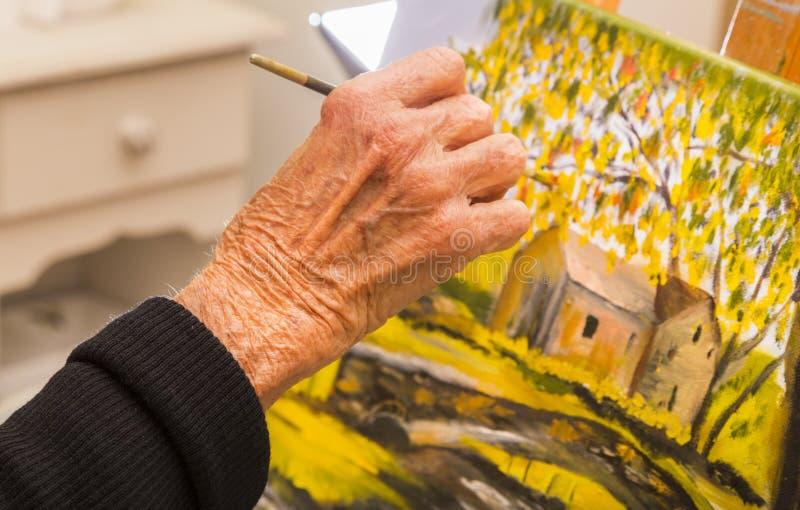 Het hogere vrouw schilderen, close-up van de borstel van de handholding stock afbeelding