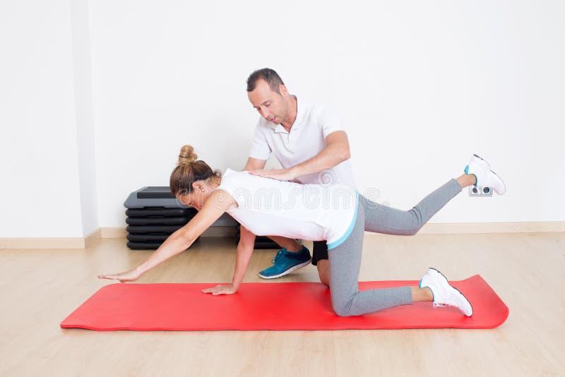 Het hogere vrouw uitrekken zich met fysiotherapeut stock foto's