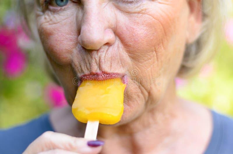 Het hogere vrouw zuigen op een bevroren oranje lollie royalty-vrije stock fotografie