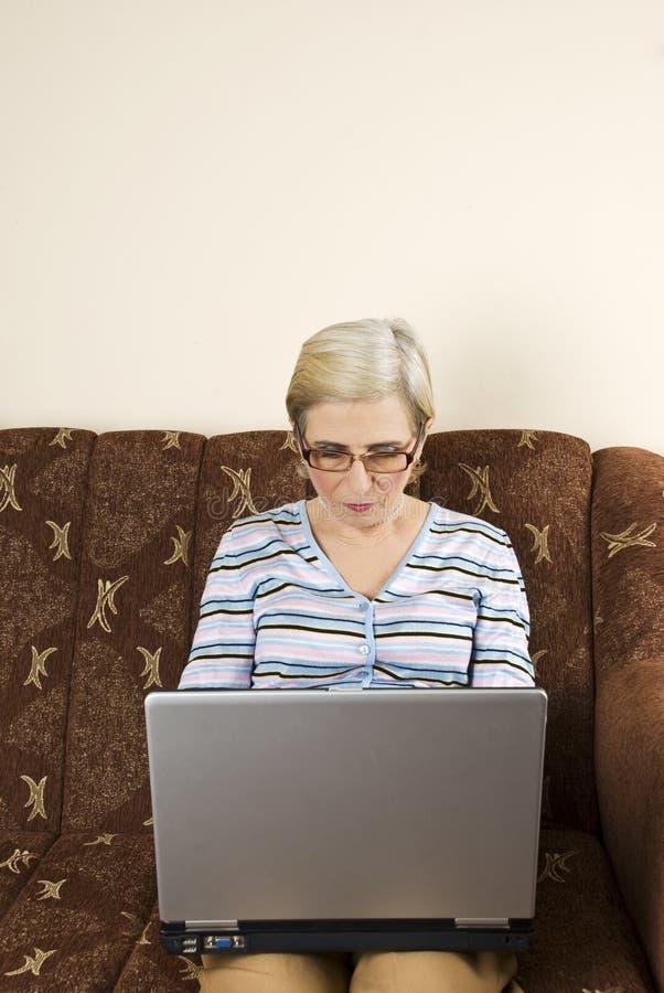 Het hogere vrouwenwerk aangaande laptop royalty-vrije stock afbeelding