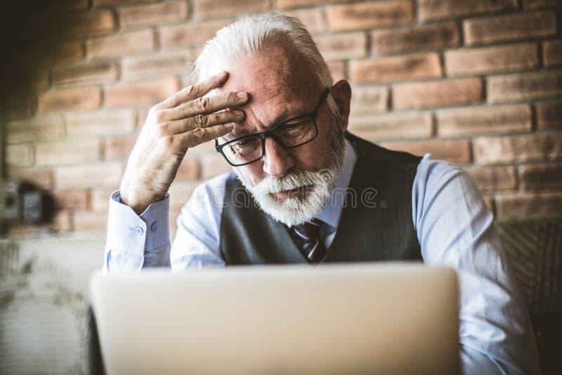 Het hogere zakenman werken De harde zaken maken hoofdpijn stock afbeeldingen