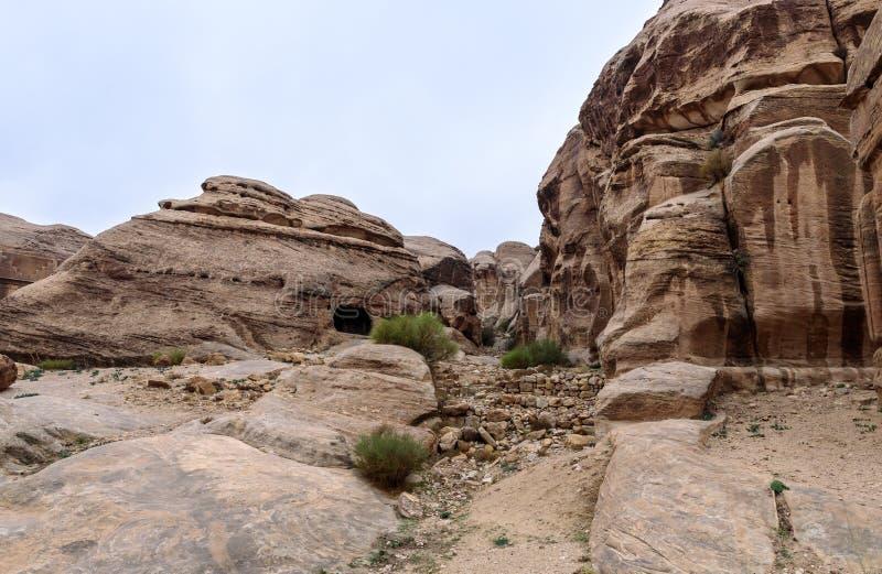 Het hol in de rots dichtbij de weg die tot Petra leiden - het kapitaal van het Nabatean-koninkrijk in Wadi Musa-stad in Jordanië stock afbeeldingen