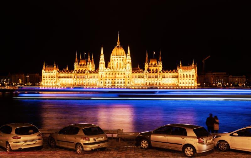 Het Hongaarse parlement bij nacht met paar die mooie mening in Boedapest, Hongarije bekijken royalty-vrije stock afbeelding