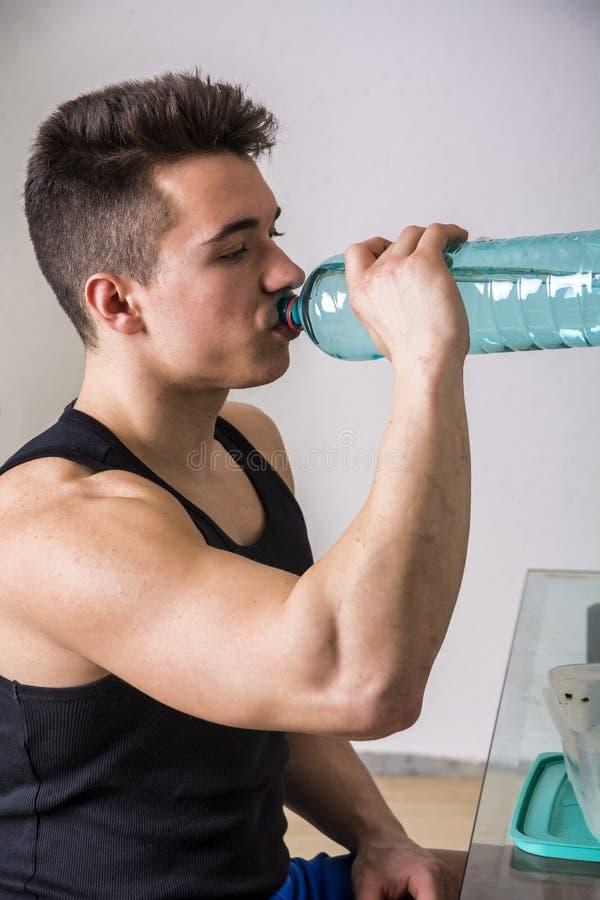 Het hongerige spier jonge mens gulping onderaan voedsel stock afbeelding