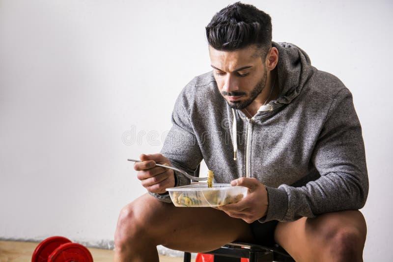 Het hongerige spiermens gulping onderaan voedsel stock fotografie