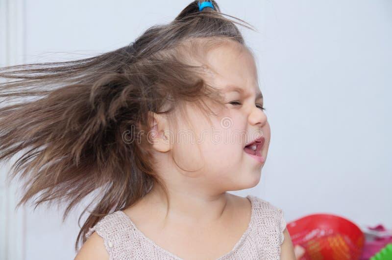 Het hoofd bespattende haar van meisjeschokken grappig kind met het expressieve emotie dansen royalty-vrije stock afbeeldingen