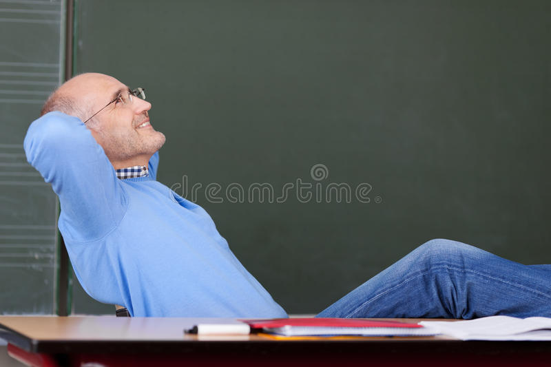 Het Hoofd die van leraarswith hands behind omhoog Bureau bekijken royalty-vrije stock afbeelding