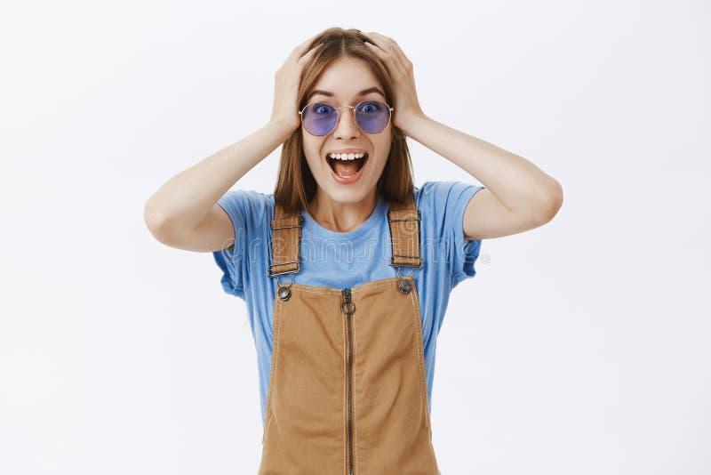 Het hoofd gaan rond van geluk en verbazing Portret van blije opgetogen vrolijke jonge vrouw in bruine overall en stock fotografie