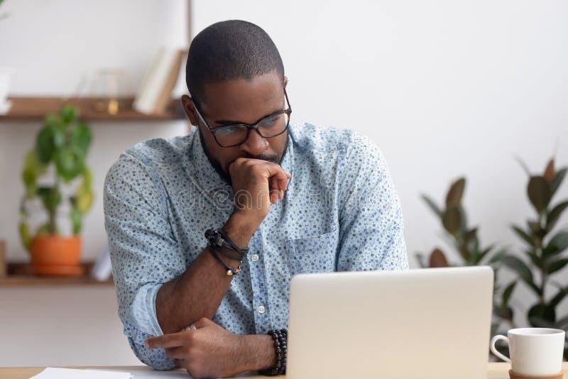 Het hoofd schoot ernstige in verwarring gebrachte Afrikaanse Amerikaanse zakenman die laptop bekijken stock afbeelding