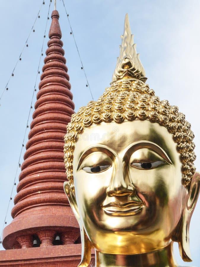 Het hoofd van het gouden standbeeld van Boedha en de bovenkant van bruin mozaïek beëindigden pagode met blauwe hemelachtergrond stock afbeeldingen