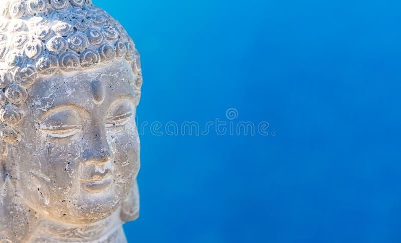 Het hoofdstandbeeld van Boedha met blauwe waterachtergrond royalty-vrije stock foto's