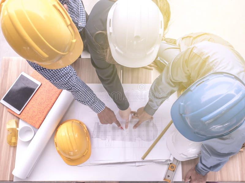 Het hoogste concept, de Ingenieur en de arbeiders die van het meningsgroepswerk project van de nieuwe bouw bespreken , Team van a stock afbeeldingen