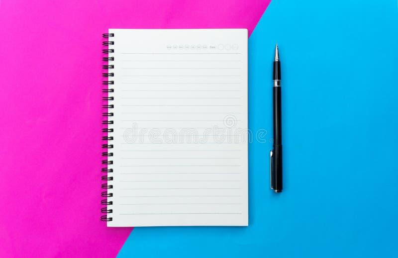 Het hoogste menings lege notitieboekje en de zwarte pen voor modelvlakte leggen op blauwe en roze achtergrond royalty-vrije stock afbeelding