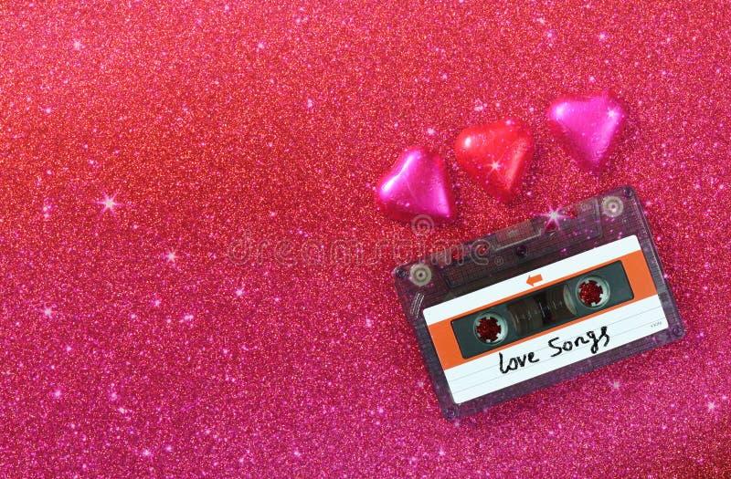 Het hoogste meningsbeeld van de kleurrijke chocolade van de hartvorm en de audiocassette op rood schitteren achtergrond royalty-vrije stock foto