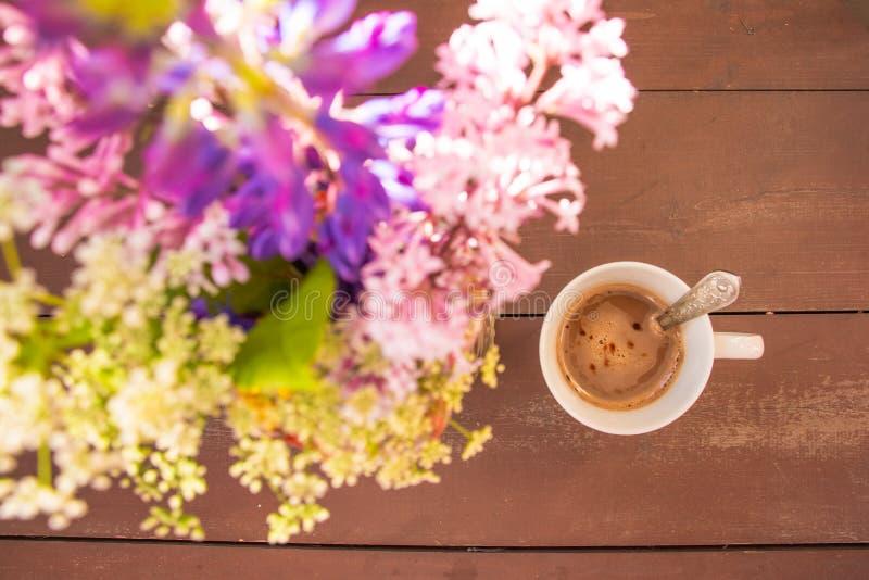 Het hoogste meningsbeeld van de kleurrijke zomer bloeit naast kop van koffie op houten lijst wijnoogst Het concept van het ochten royalty-vrije stock foto