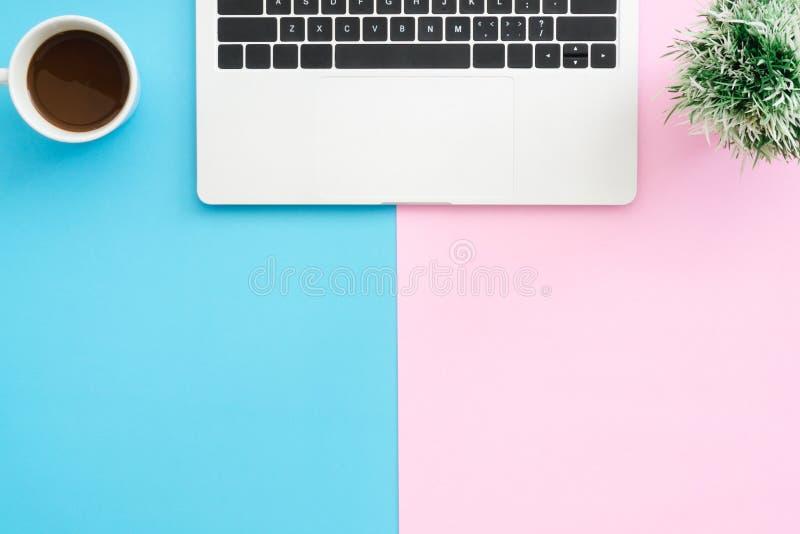 Het hoogste meningsbureau met laptop, de installatie en de koffie vormen op blauwe roze kleurenachtergrond tot een kom stock foto