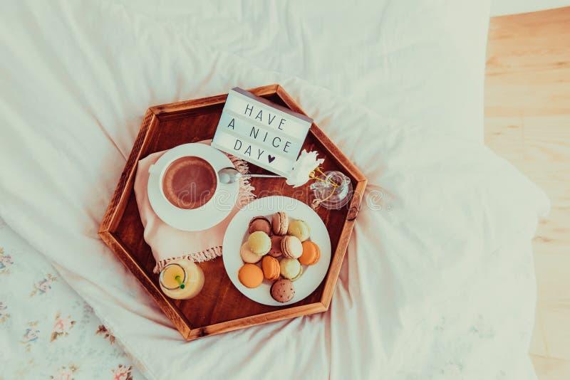 Het hoogste meningsontbijt in bed met heeft een aardige dagtekst op aangestoken vakje Koffie, sap, makarons, bloem in vaas op hou royalty-vrije stock fotografie
