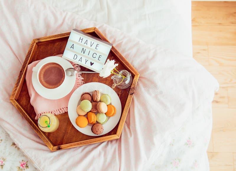 Het hoogste meningsontbijt in bed met heeft een aardige dagtekst op aangestoken vakje Kop van koffie, sap, makarons, bloem in vaa royalty-vrije stock fotografie