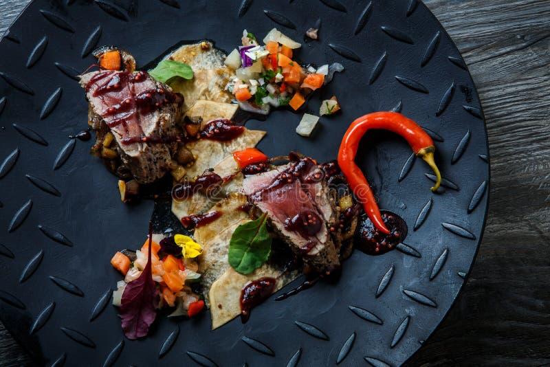 Het hoogste middelgrote ruwe geroosterde vlees van de meningsclose-up met Spaanse peper en saus royalty-vrije stock foto's