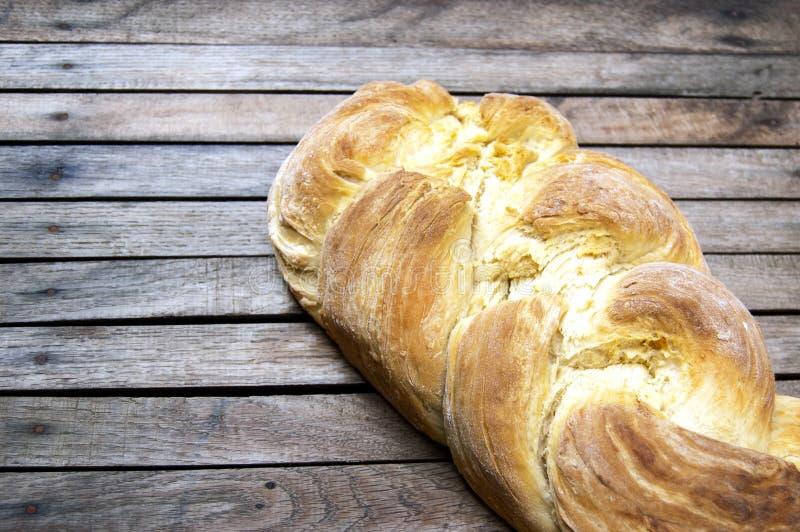Het hoogste schot, sluit omhoog van vers gebakken eigengemaakt veganist gevlecht brood op een houten, rustieke lijstachtergrond,  royalty-vrije stock afbeelding