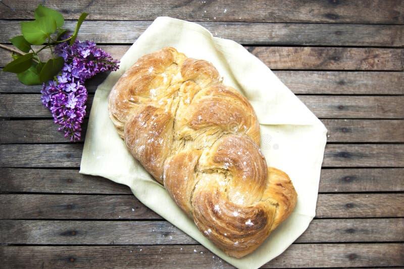 Het hoogste schot, sluit omhoog van vers gebakken eigengemaakt veganist gevlecht brood op een houten, rustieke lijstachtergrond,  stock foto