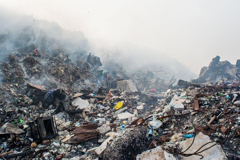Het hoogtepunt van de het gebiedsmening van de huisvuilstortplaats van rook, draagstoel, plastic flessen, vuilnis en ander afval  stock foto
