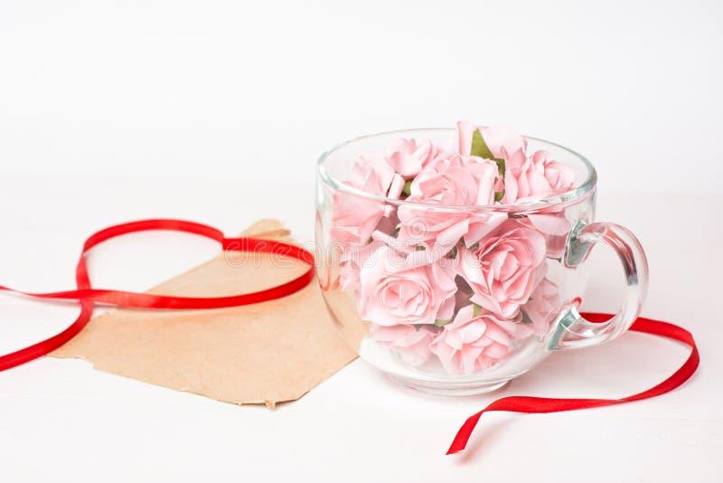 Het hoogtepunt van de glaskop van roze rozen met document blad stock foto's