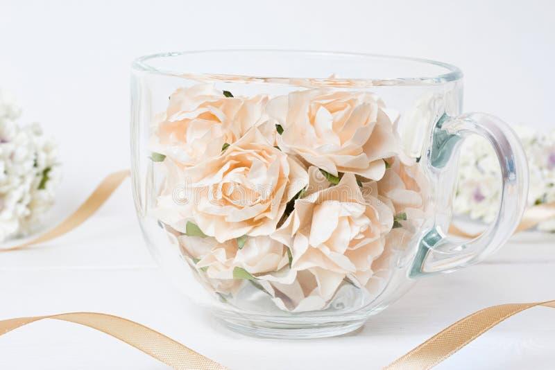 Het hoogtepunt van de glaskop van witte rozen met lint op houten lijst royalty-vrije stock afbeeldingen