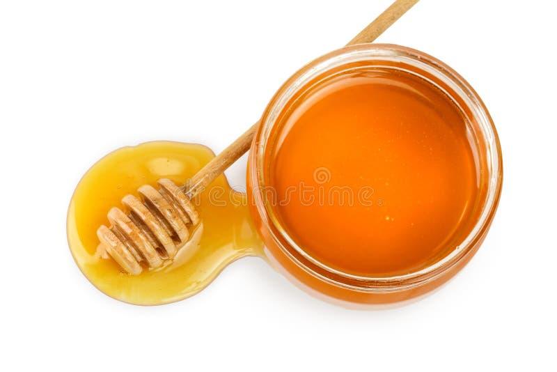 Het hoogtepunt van de glaskruik van honing en stok op witte achtergrond wordt ge?soleerd die royalty-vrije stock afbeelding