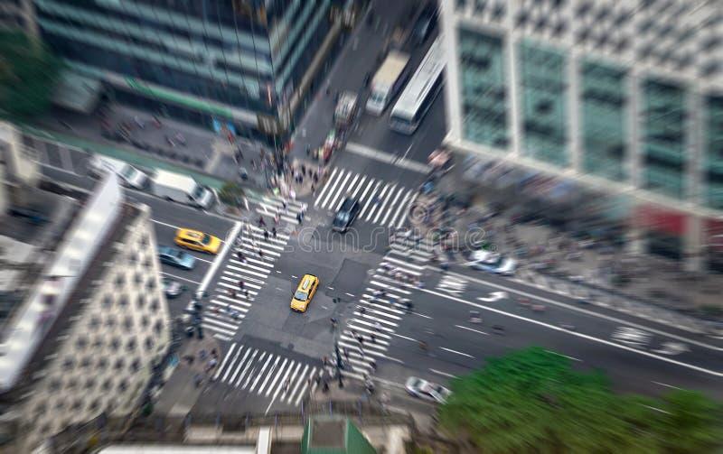 Het hoogtepunt van de de stadsstraat van New York van taxis, auto's en voetgangers Gele cabine in nadruk Bezige NYC de stad in royalty-vrije stock afbeelding