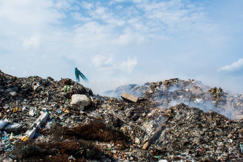 Het hoogtepunt van de de streekmening van de huisvuilstortplaats van rook, draagstoel, plastic flessen, vuilnis en afval bij het  royalty-vrije stock afbeeldingen
