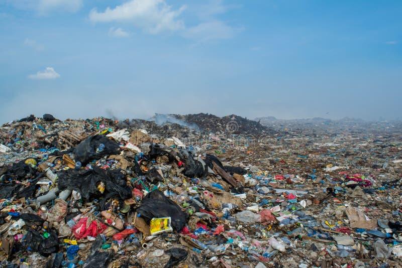 Het hoogtepunt van de de streekmening van de vuilnisstortplaats van rook, draagstoel, plastic flessen, huisvuil en afval bij het  royalty-vrije stock afbeelding